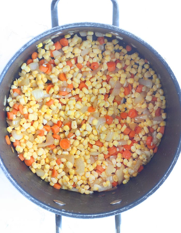 sauteeing the corn and vegetables in a large stock pot