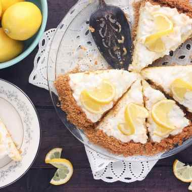 sliced lemon icebox pie with a plated piece of pie and a bowl of lemons to the side