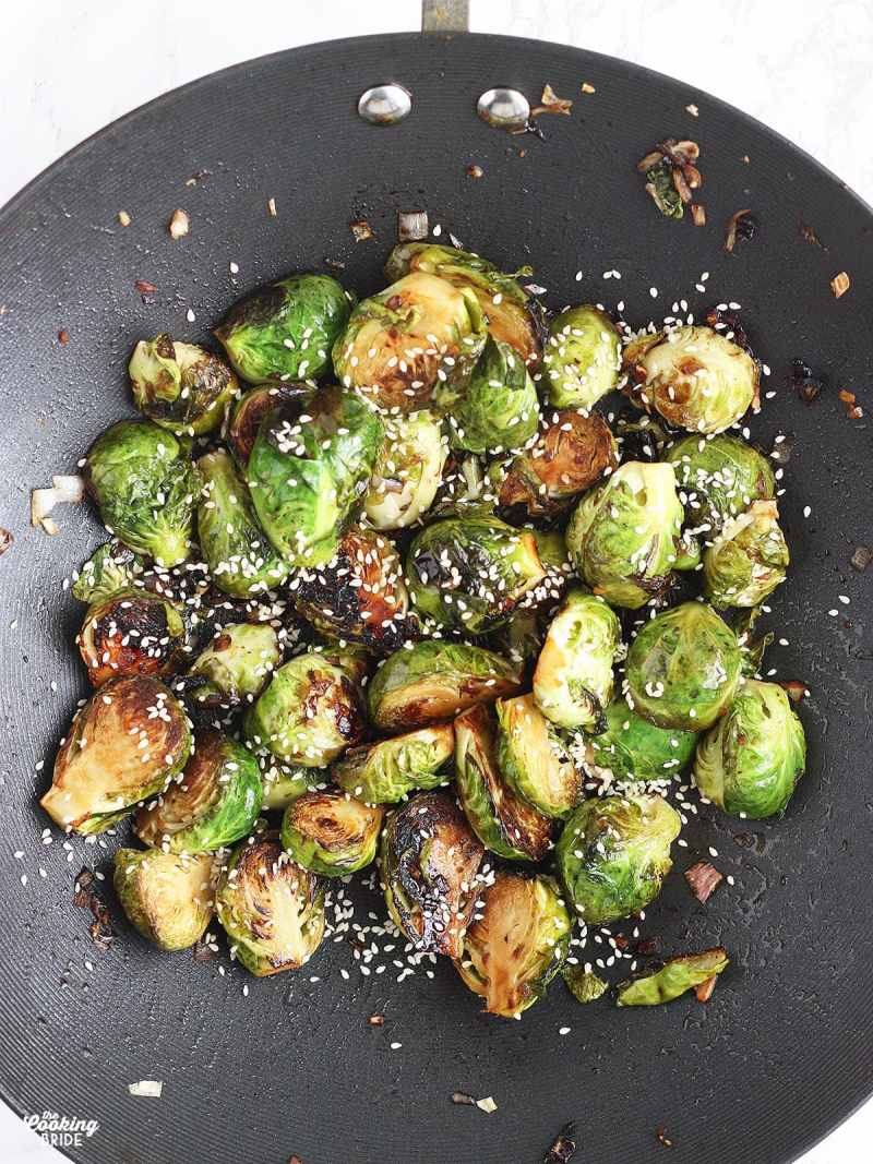 Stir Fried Brussels sprouts garnished with sesame seeds in a wok.