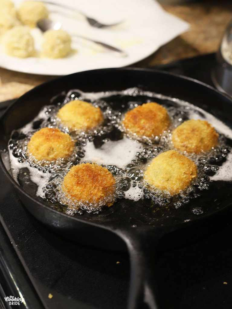 six boudin balls frying in a cast iron skillet