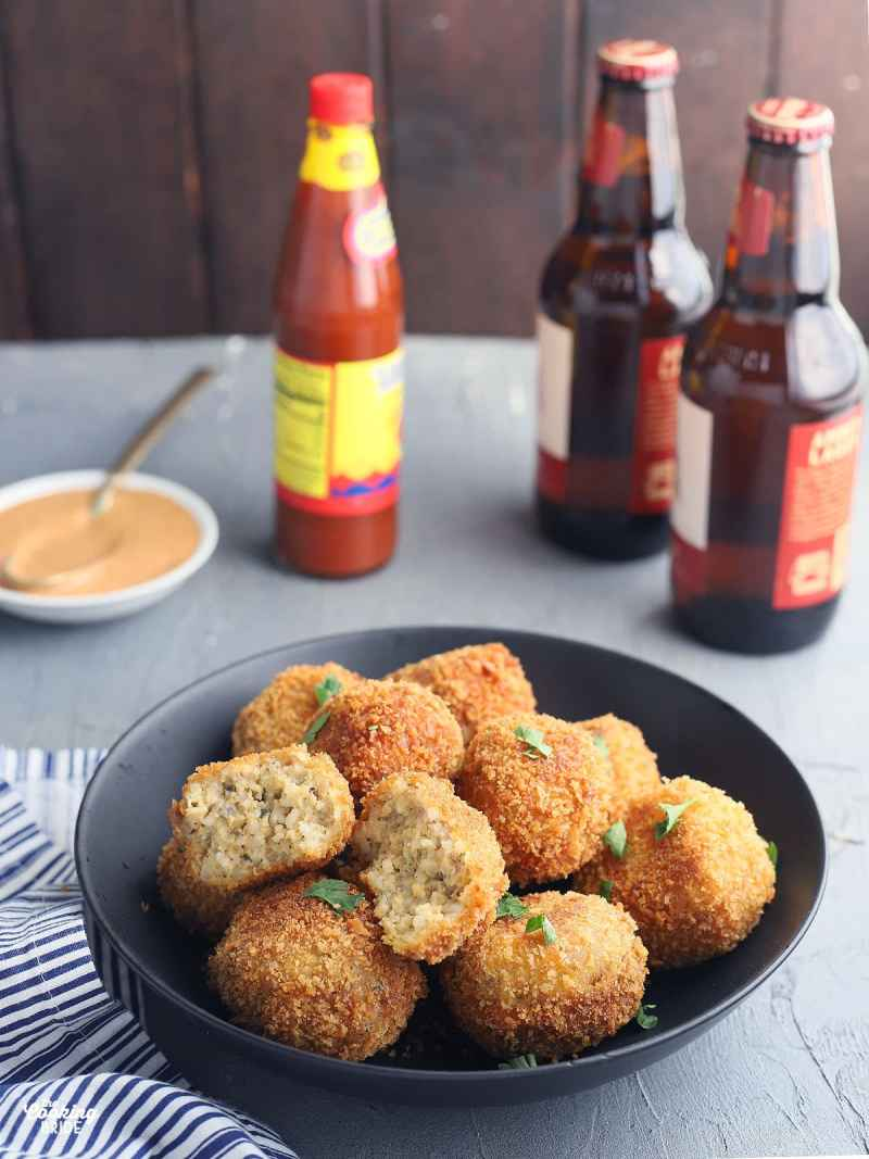 fried boudin balls in a black serving bowl with a small dish of dipping sauce, hot sauce and two bottles of beer in the background