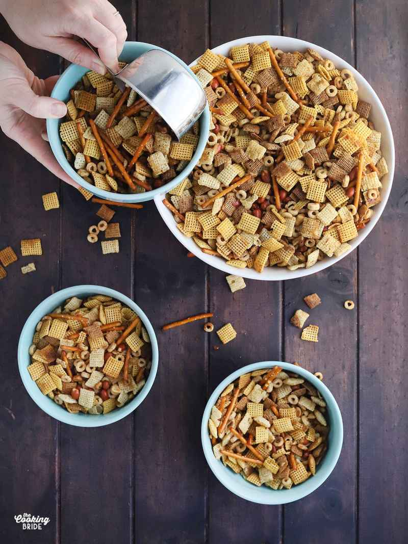 hand using a metal measuring cup to measure out homemade chex mix into blue serving bowls