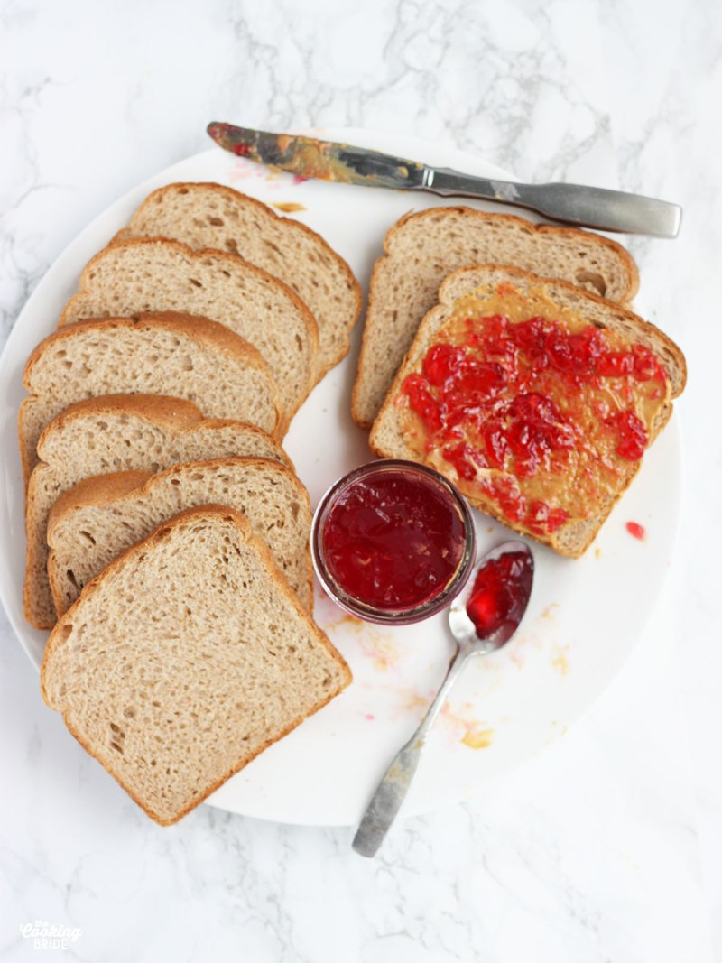 plate of sliced bread with peanut butter and plum jelly
