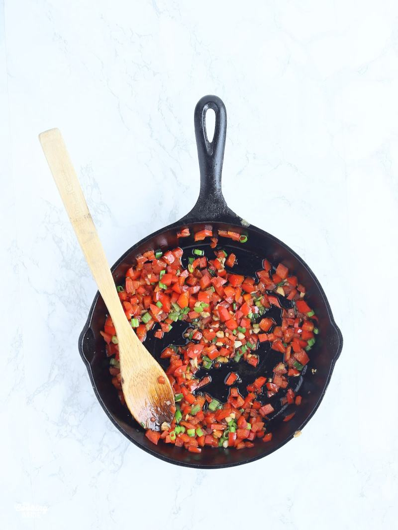 wooden spoon in a skillet with sauteed bell peppers, green onions and minced garlic