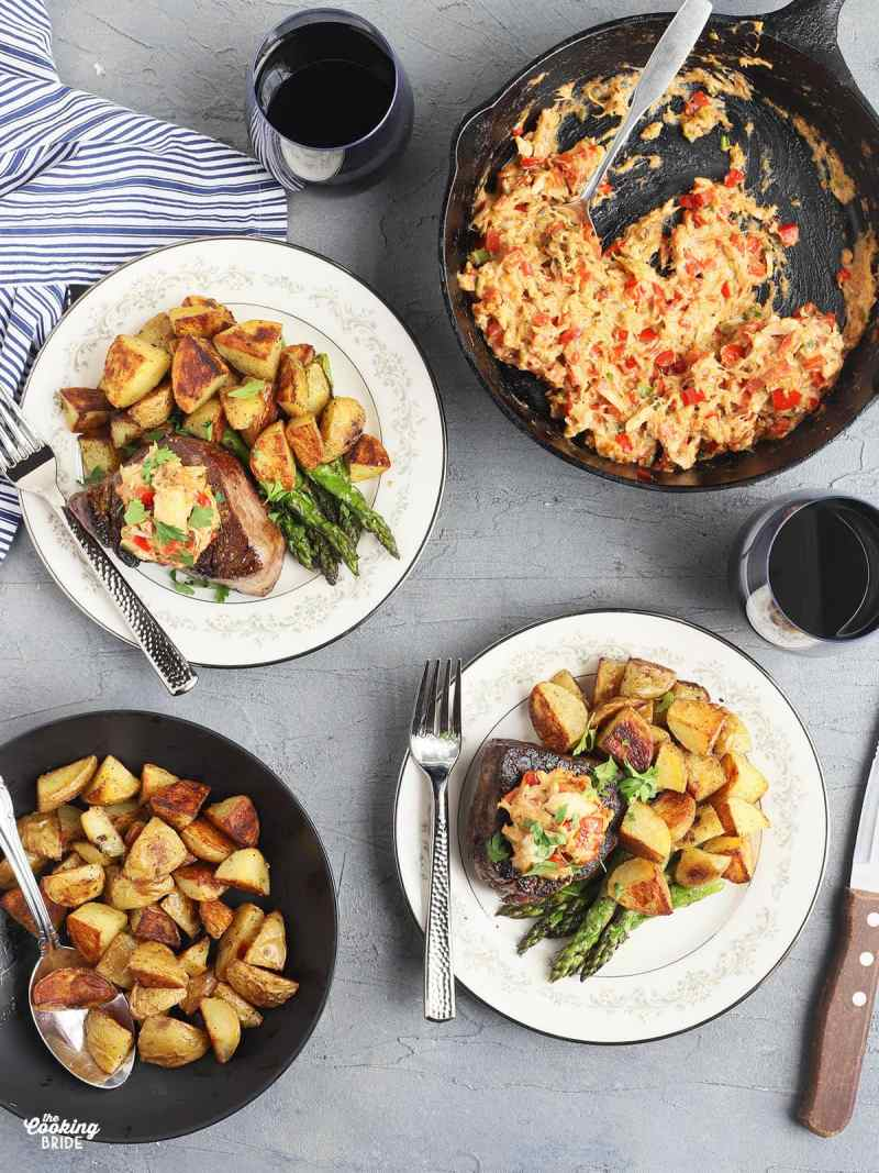 overhead shot of two filets on white China plates garnished with crab topping and served with roasted potatoes and asparagus. A skillet of crab topping, a bowl of roasted potatoes and two glasses of red wine are to the side