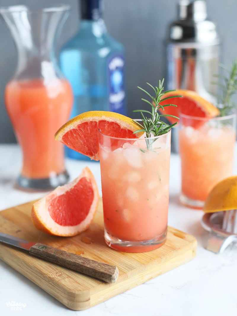 rosemary and gin grapefruit cocktail in a glass of ice garnished with a grapefruit wedge and a sprig of rosemary, slice of grapefruit and a knife to the side with another cocktail, grapefruit juice, bottle of gin and shaker in the background