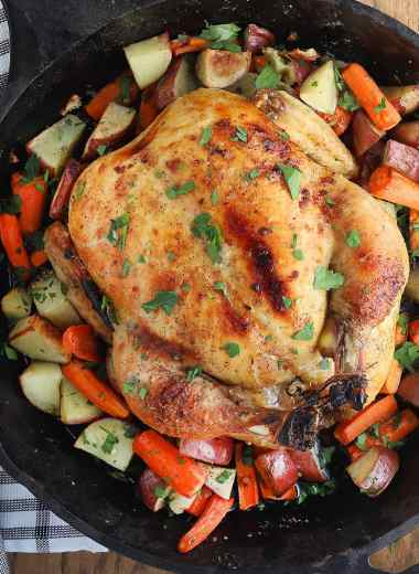 overhead shot of cast iron roast chicken with roasted vegetables, black and white dish towel, meat fork and carving knife to the side
