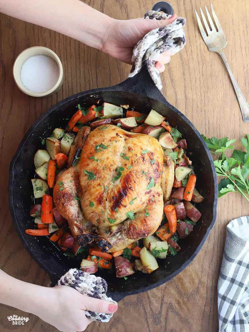 hands placing a cast iron skillet of roasted vegetables and whole chicken onto a table