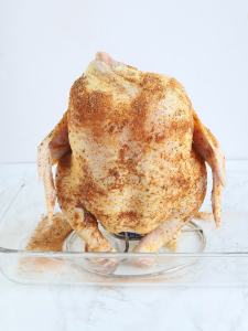 uncooked drunk chicken on a roaster sitting in a glass casserole dish