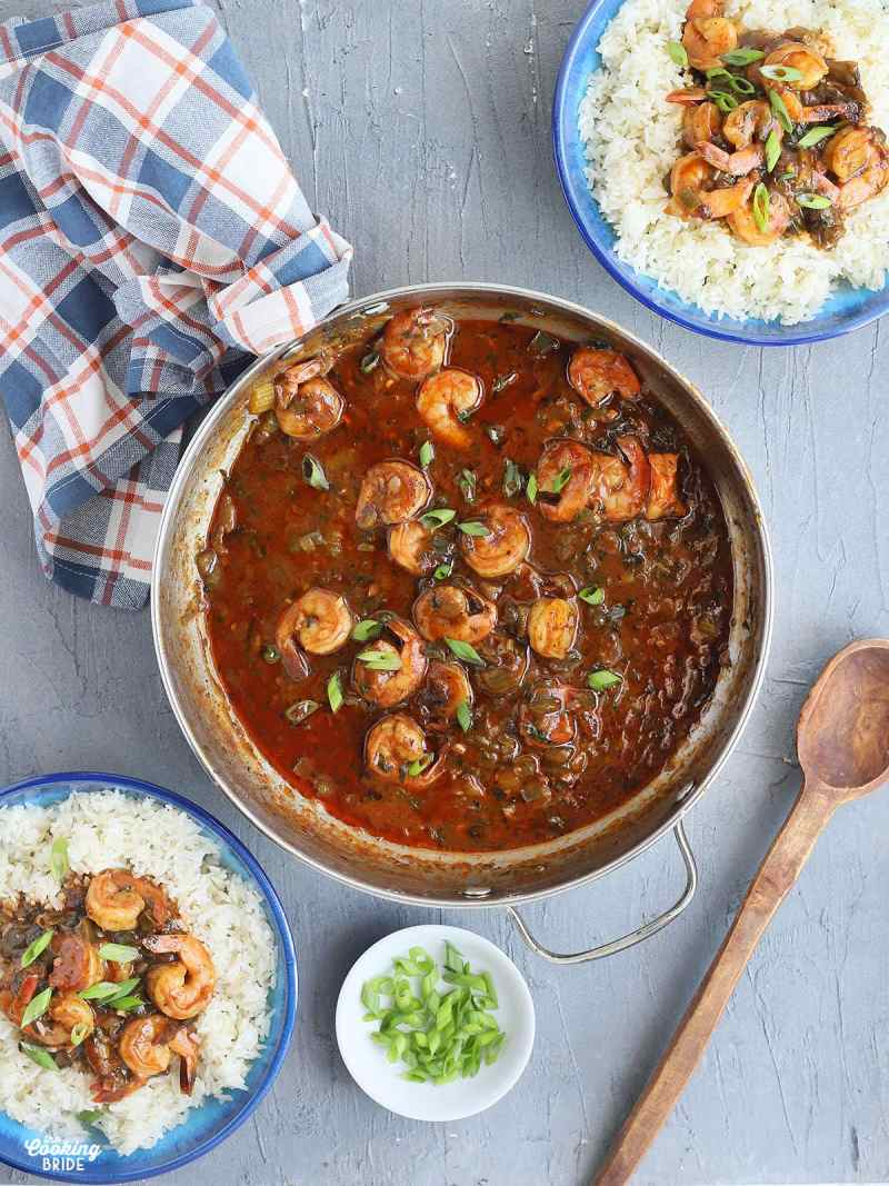 metal saucepan with cooked shrimp in gravy, two blue bowls of Cajun shrimp and rice garnished with green onions and a wooden serving spoon to the side