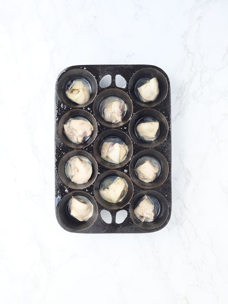 raw oysters in a muffin pan
