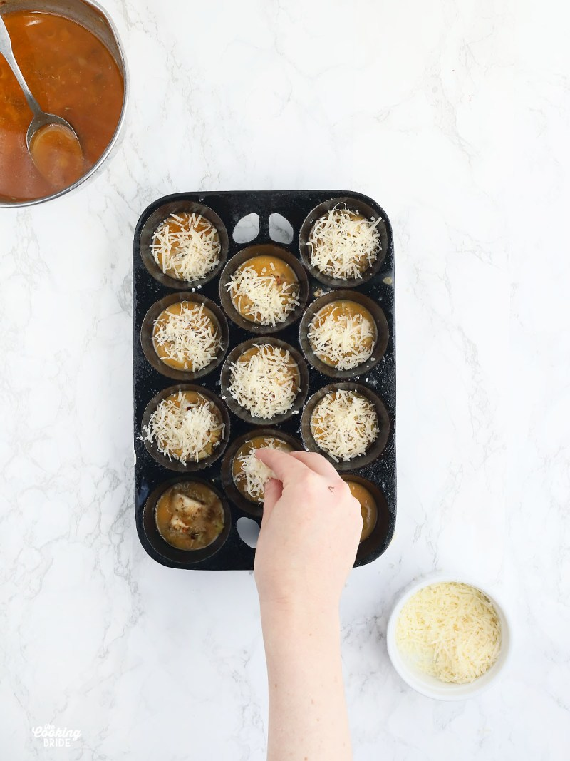 hand sprinkling parmesan cheese over the tops of oysters in a muffin pan