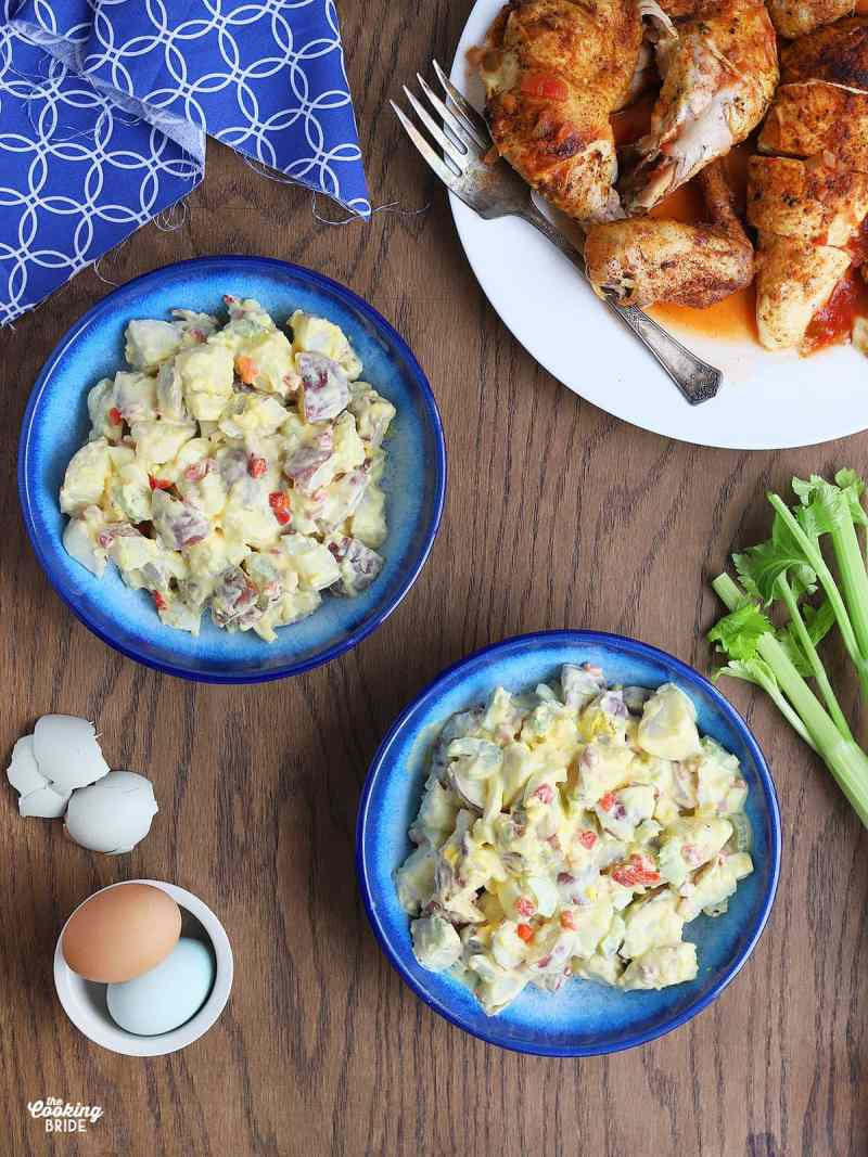 overhead shot of two blue bowls filled with potato salad, celery stalks, colorful hardboiled eggs and roast chicken to the side