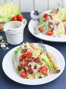 side view of a plated wedge salad with a small pitcher of dressing, platter of unserved salads and iceberg lettuce wedges in the background