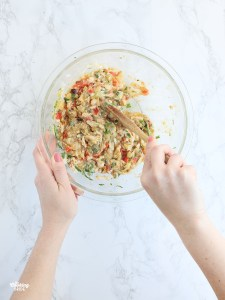 hand stirring crab cake mixture in a large glass mixing bowl