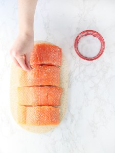 hand seasoning four salmon fillets with salt