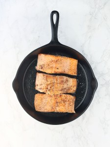 salmon filets in a cast iron skillet skin side down