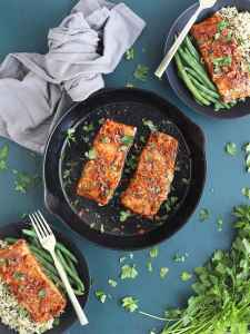 overhead shot of two glazed salmon fillets in a cast iron skillet with two filets in black serving bowls on either side