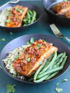 a glazed salmon filet on a bed of rice and fresh green beans in a black bowl