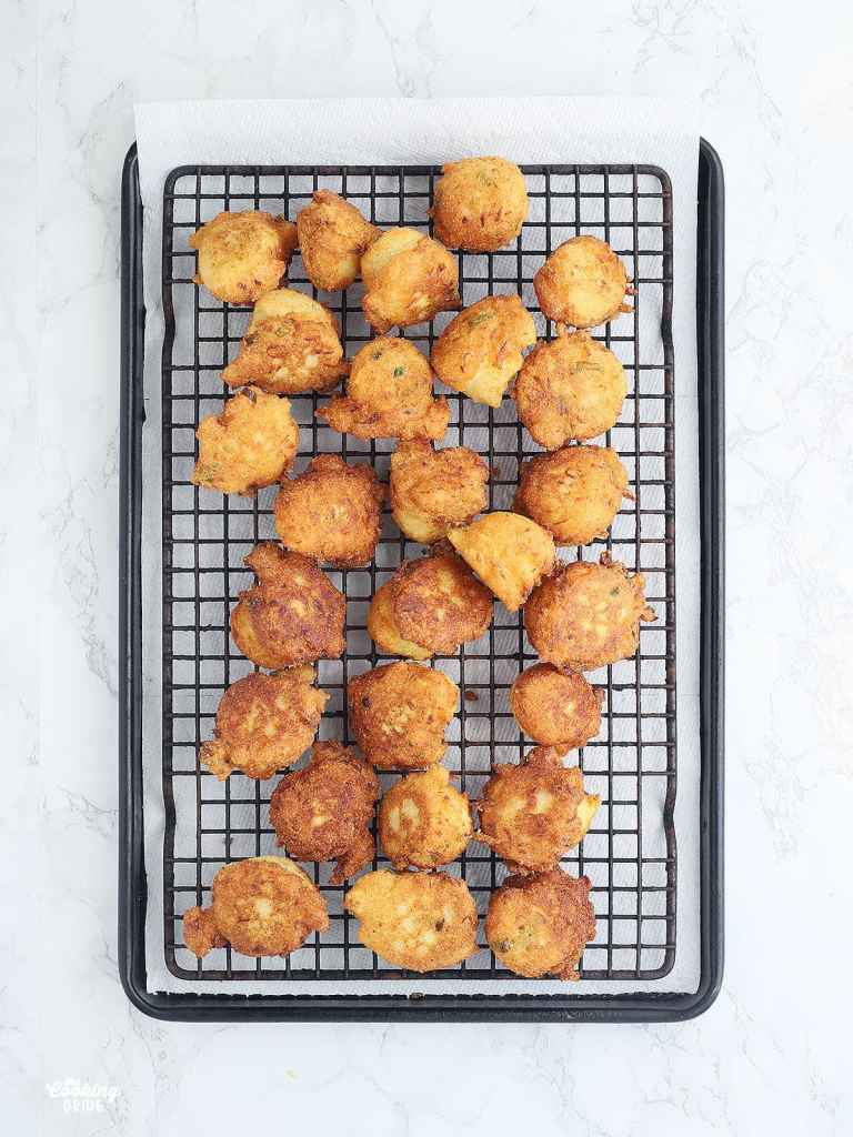 fried squash puppies draining on a lined baking sheet