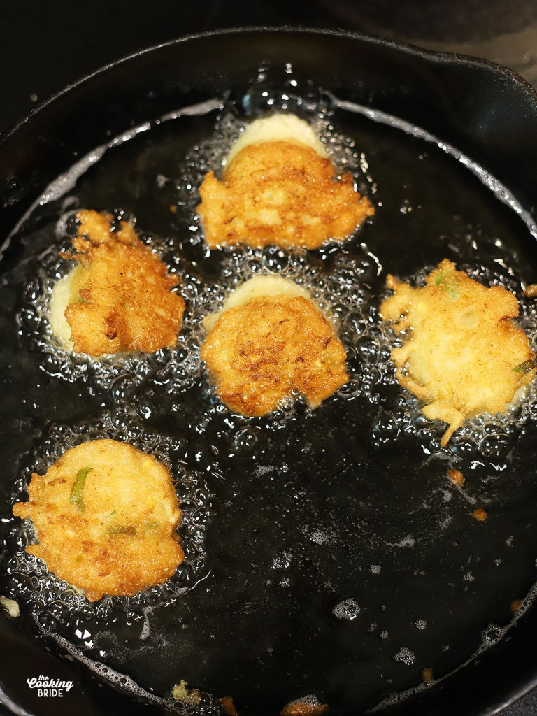 squash puppies frying in oil in a cast iron skillet