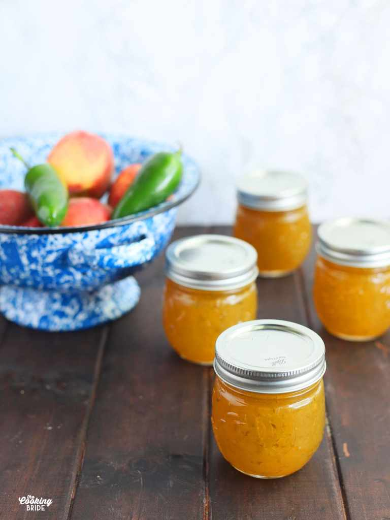 Four jars of peach jalapeno on a dark wooden table. Blue and white colander of peaches and jalapeno peppers.