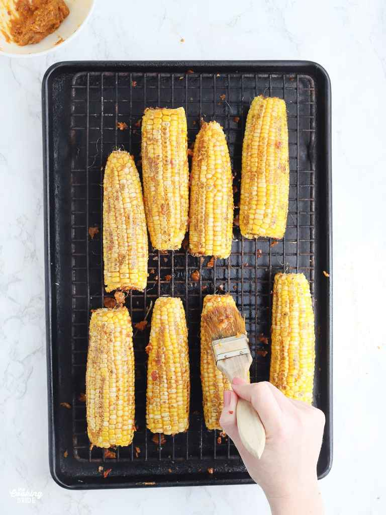hand brushing bacon butter over a rack of roasted corn