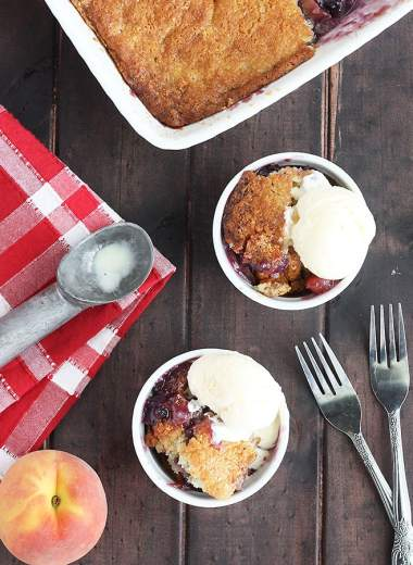 overhead shot of two bowls of blueberry peach cobbler with vanilla ice cream. Pan of cobbler, two forks, ice cream scoop and fresh peach to the side.