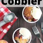 overhead shot of two bowls of blueberry peach cobbler with vanilla ice cream.