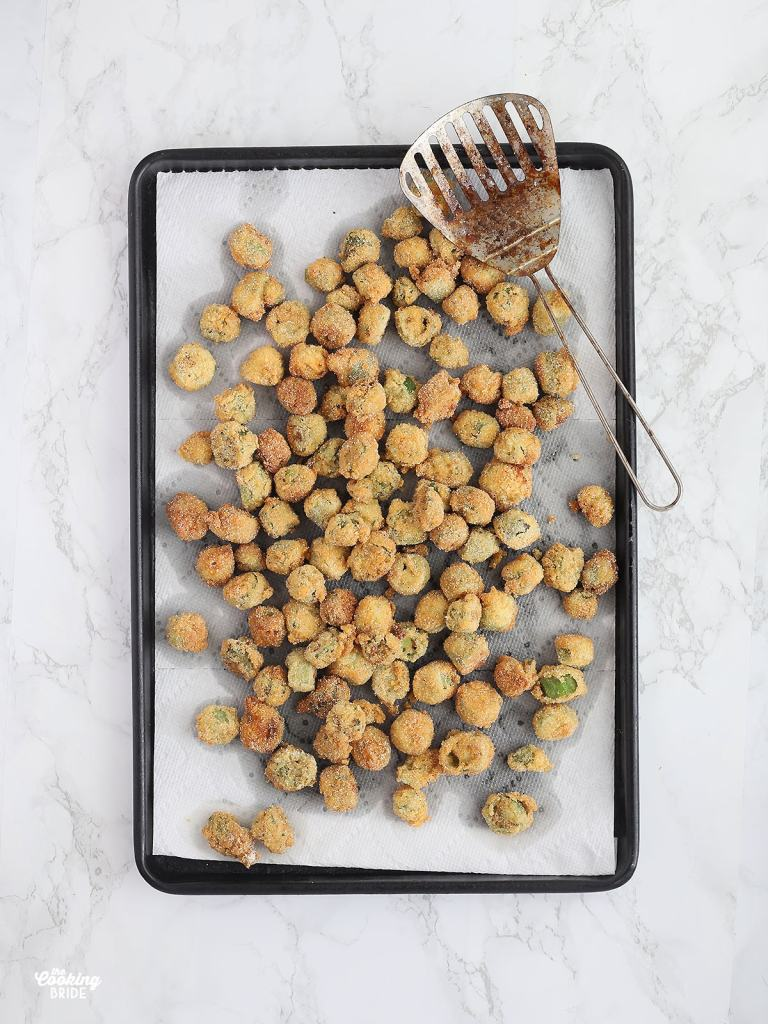 fried okra draining on a paper towel lined baking sheet