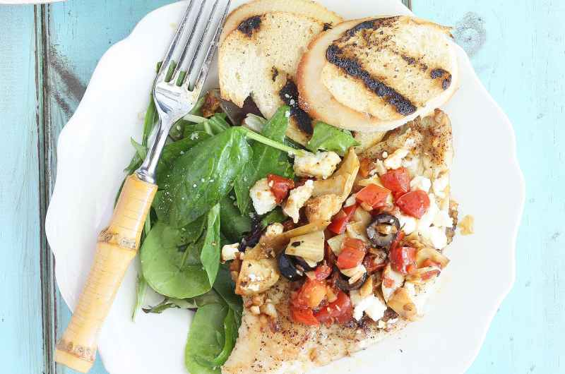 Seasoned catfish fillets topped with artichoke hearts, black olives, tomatoes and feta cheese on a white plate with a fork and toasted bread