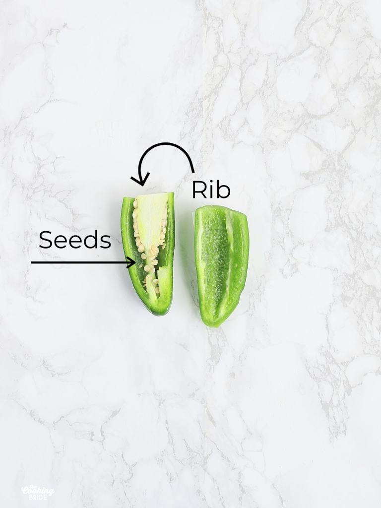 jalapeno pepper sliced in half to show seeds and rib.