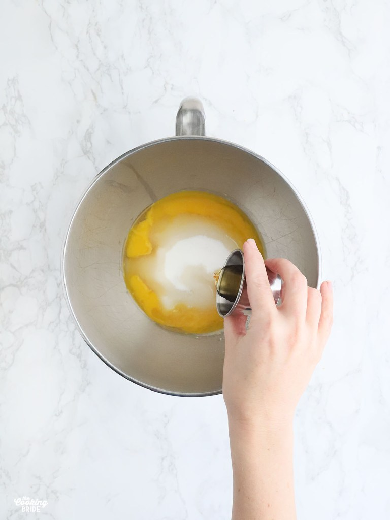hand pouring vanilla extract into a stainless steel mixing bowl with egg yolks and sugar