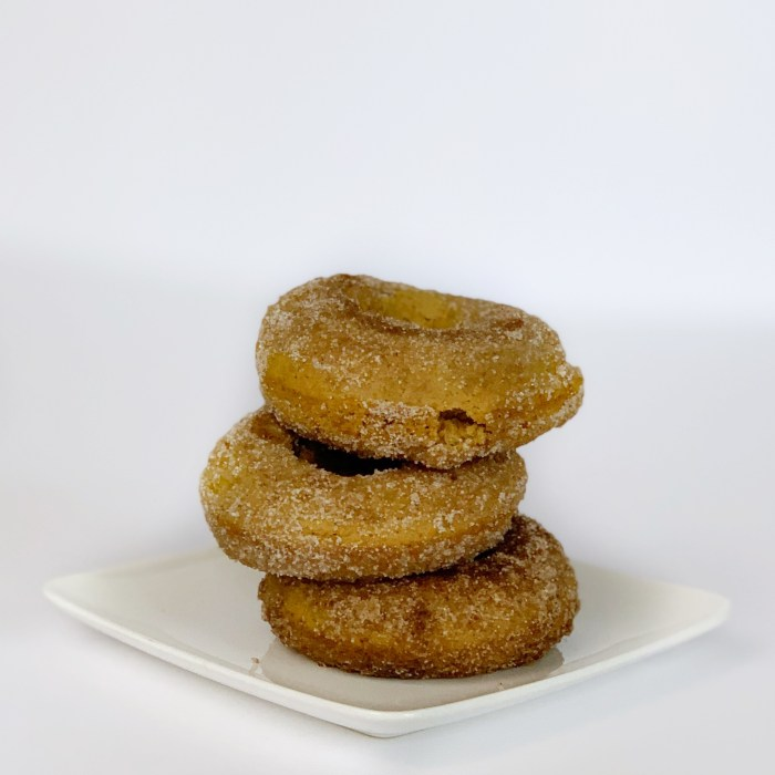 a stack of three pumpkin spiced donuts on a plate