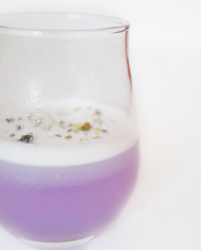 a purple ombre cocktail garnished with flowers