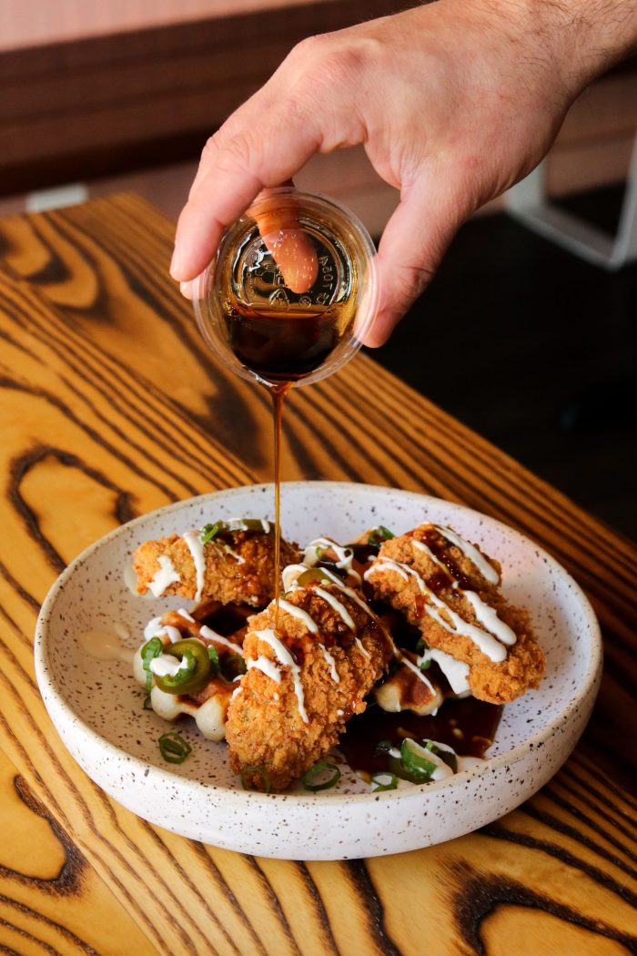 A hand pouring maple syrup on a plate of chicken and waffles