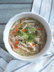 chicken veggies porridge in a white bowl.