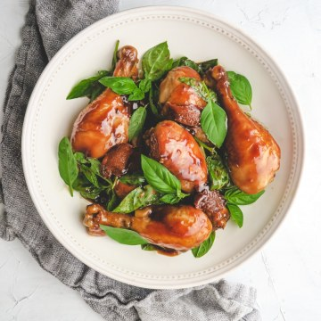 ooked three cup chicken drumsticks with basil in a white plate on top of gray linen cloth.