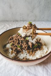 chopstick, a bowl of rice top with ground pork and scallion