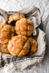 pineapple buns in a basket lined with dish towel over a white clothe.