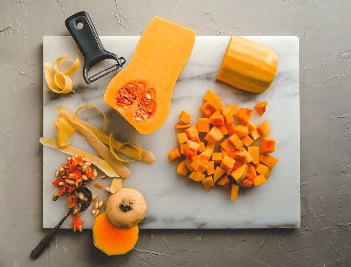 white marble cutting board with butternut squash cut up in cubes and skinned in halves.