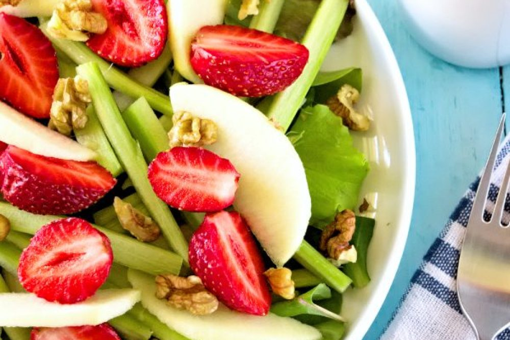 summer salad in a plate - greens, rhubarb, apples and walnut on top