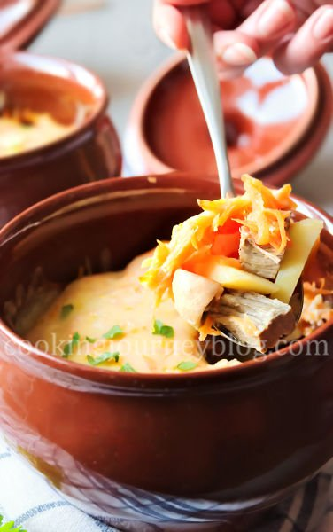 Dinner in a clay pot. Beef and potatoes, covered with cheese and parsey in a spoon.