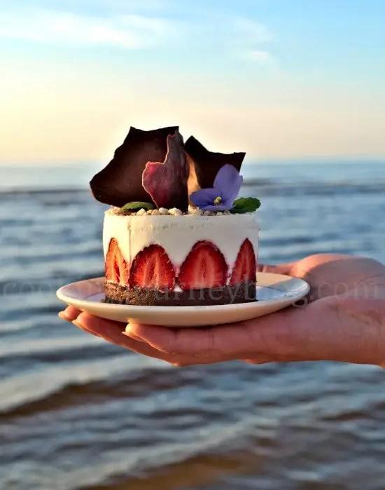 Holding No Bake Greek Yogurt Dessert in one hand on the seaside