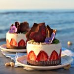 No Bake Greek Yogurt Dessert, decorated with chocolate and strawberries, on a white plate on the seaside