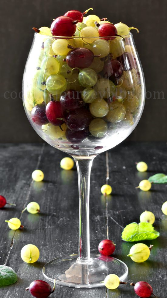 Green and red gooseberries in a wine glass on a black table