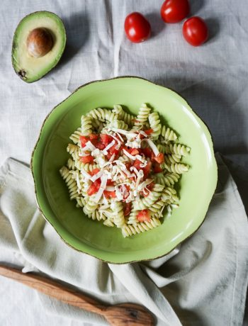 green plate with fusilli pasta, avocado sauce and cherry tomatoes
