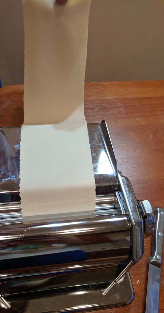 Rolling gyoza skin in a pasta roller
