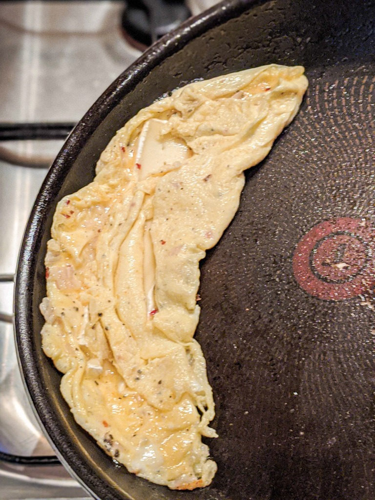 Scoot the French omelette to the edge and the egg will naturally fold over on itself