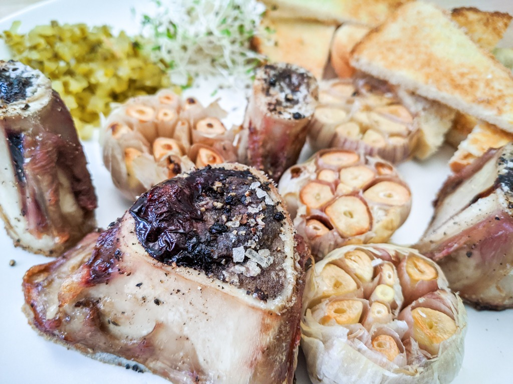 roast bone marrow seasoned with salt and freshly cracked black pepper. Paired with toast points, roast garlic, chopped pickles, and sprouts